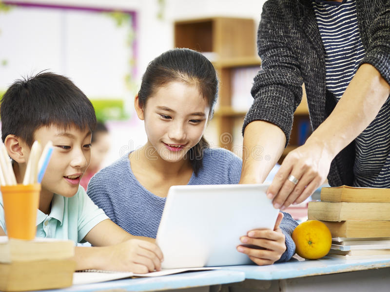 Azjatyccy podstawowi ucznie używa cyfrową pastylkę zdjęcia stock