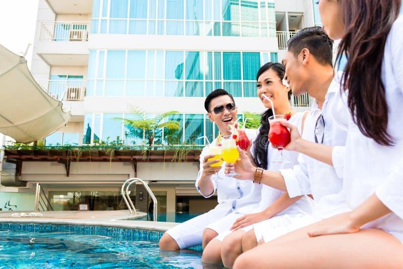 Azjatyccy przyjaciele siedzi hotelowym pływackim basenem zdjęcia royalty free