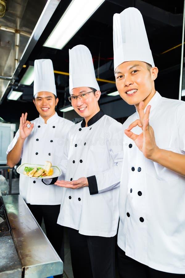 Azjatyccy szefowie kuchni w hotelowej restauracyjnej kuchni zdjęcia stock