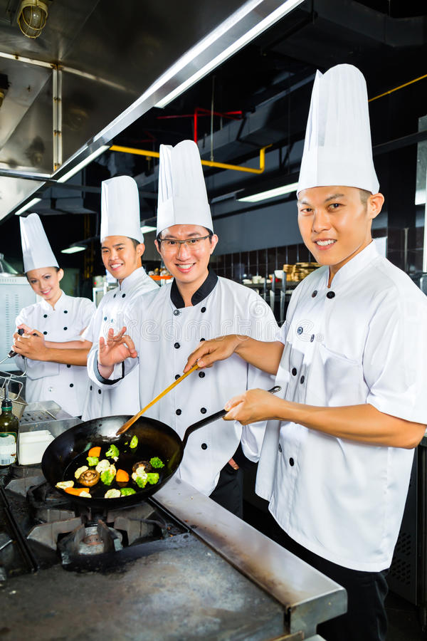Azjatyccy szefowie kuchni w restauracyjnej kuchni zdjęcia royalty free