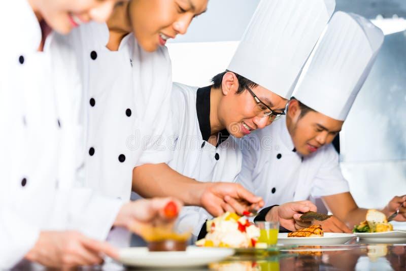Azjatyccy szefowie kuchni w restauracyjnym kuchennym kucharstwie zdjęcie stock