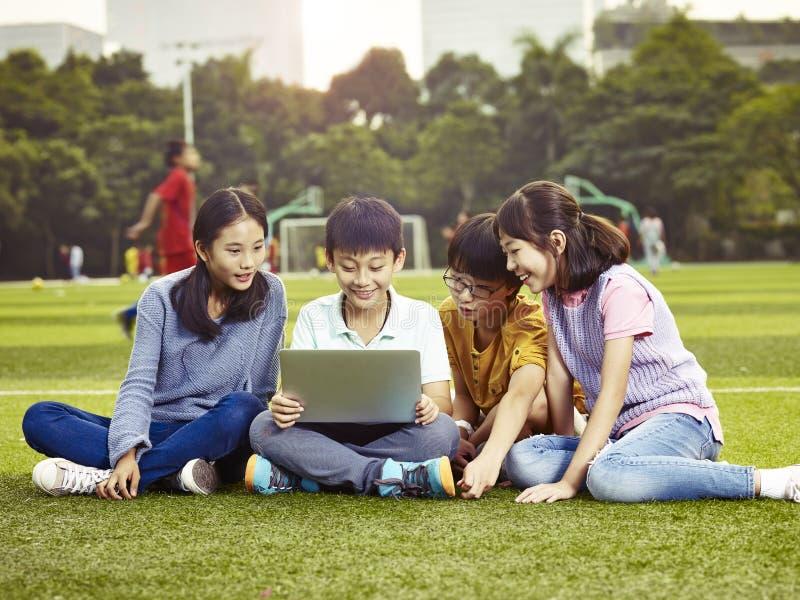 Azjatyccy szkół podstawowych dzieci używa laptop outdoors zdjęcie stock