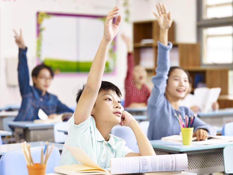 Azjatyccy szkoła podstawowa ucznie podnosi ręki w klasie obraz stock