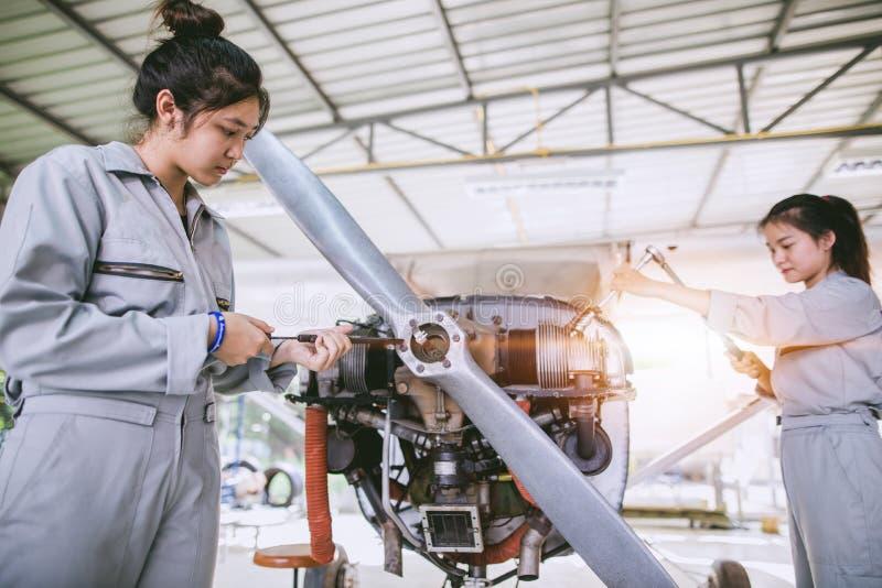 Azjatyccy uczni inżyniery, technicy i naprawiają samolot o fotografia royalty free