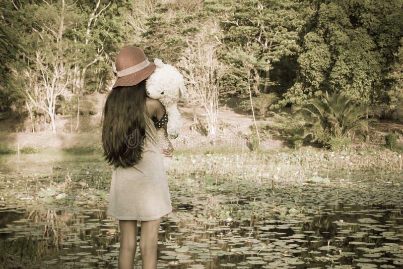 Azjatycka śliczna dziewczyna stoi samotnie przy laguną obraz stock