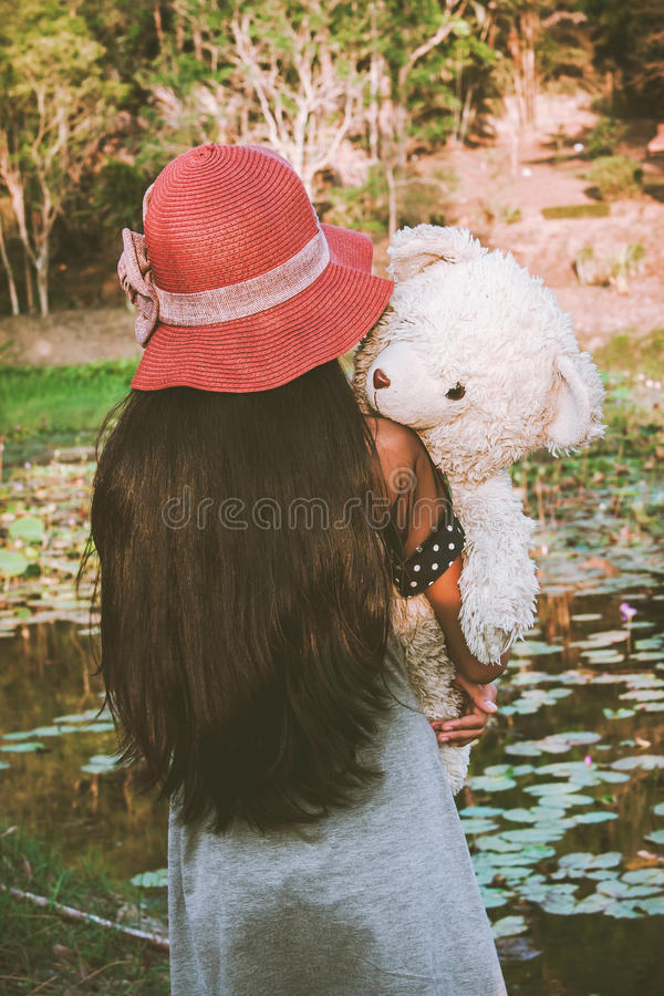 Azjatycka śliczna dziewczyna stoi samotnie przy laguny i ręki niedźwiadkowym uściśnięciem, v obraz royalty free