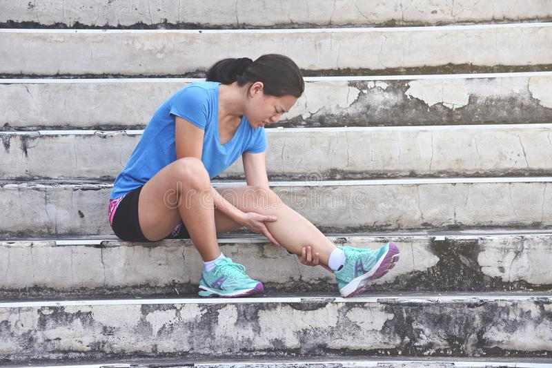 Azjatycka biegacz kobieta ma kolanową obolałość i problem po biegać obrazy stock