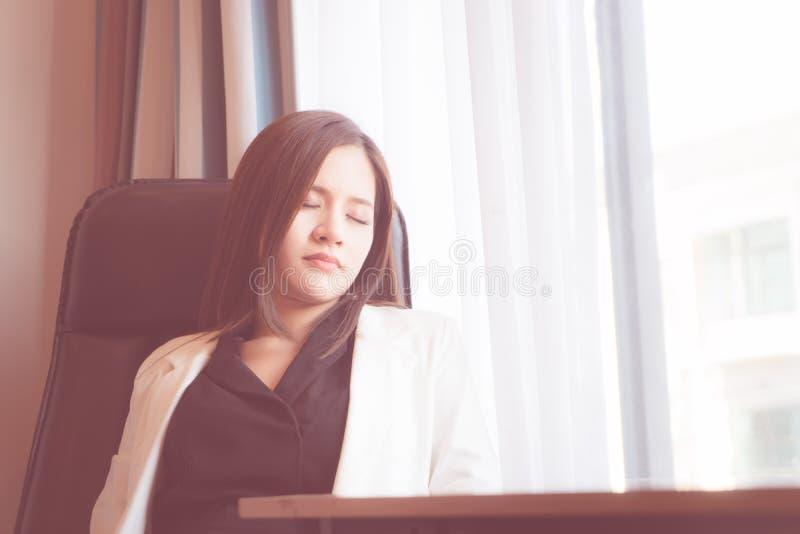 Azjatycka biurowa kobieta bierze drzemkę relaksuje w biurze fotografia royalty free
