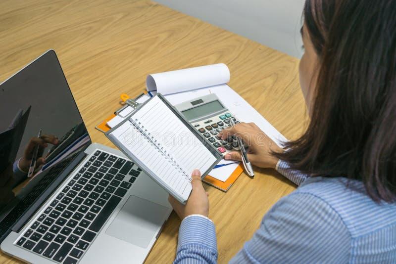 Azjatycka biurowa kobieta kalkuluje pieniężną liczbę na dokumencie zdjęcia royalty free