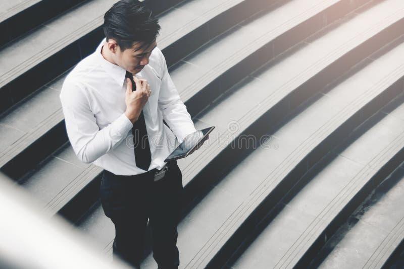 Azjatycka biznesmen pozycja na schody plenerowym i używa pastylkę obraz royalty free