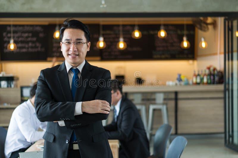 Azjatycka biznesmen pozycja, uśmiechnięty i patrzejący kamera Biznesowy pomyślny pojęcie obraz royalty free