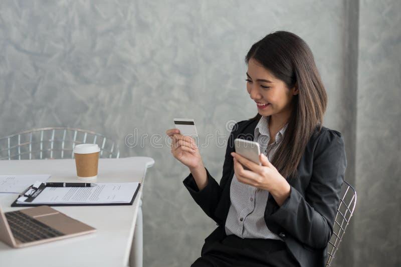 Azjatycka biznesowa dziewczyna w jej staci roboczej kupuje online z cred zdjęcie royalty free