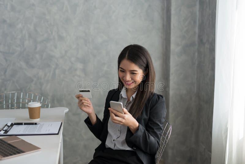 Azjatycka biznesowa dziewczyna w jej staci roboczej kupuje online z cred obraz stock