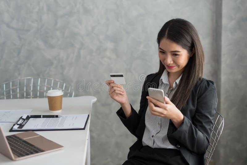 Azjatycka biznesowa dziewczyna w jej staci roboczej kupuje online z cred zdjęcia stock