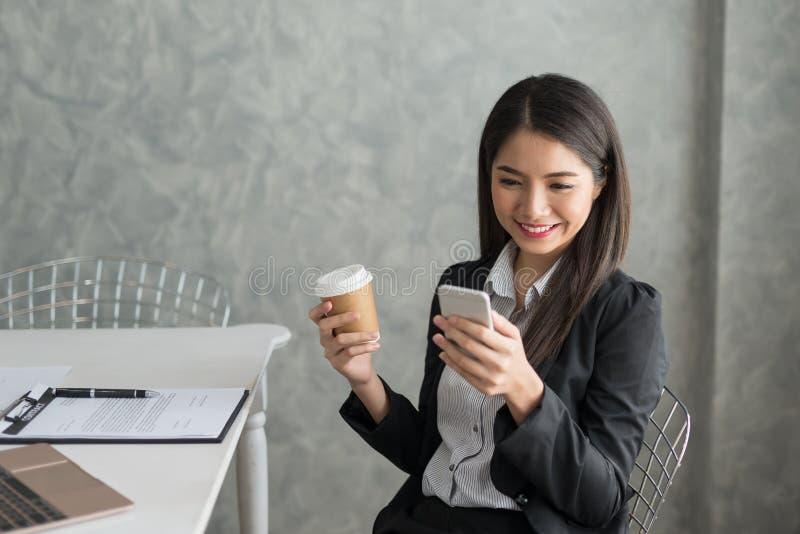 Azjatycka biznesowa dziewczyna w jej staci roboczej przy trzymać filiżankę i zdjęcie royalty free
