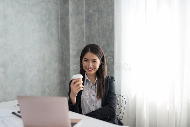 Azjatycka biznesowa dziewczyna w jej staci roboczej przy trzymać filiżankę i fotografia royalty free