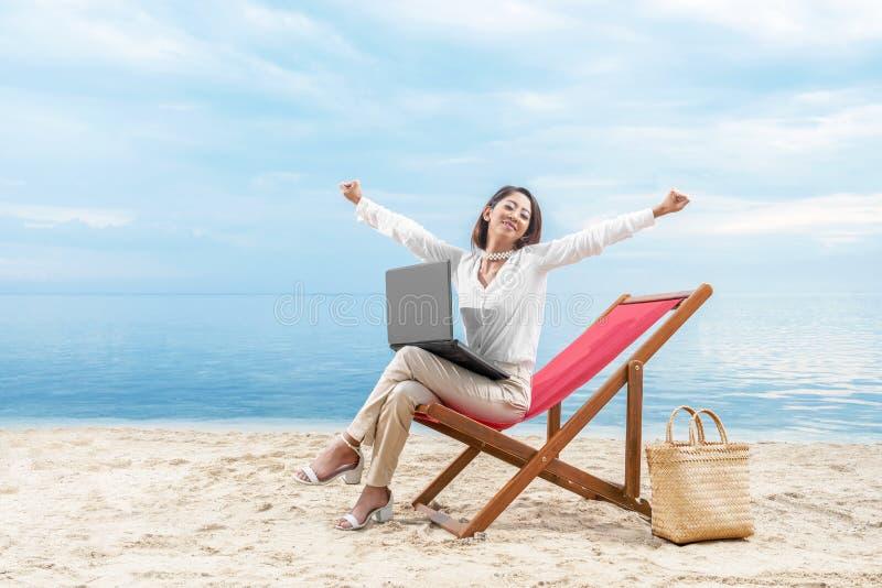 Azjatycka biznesowa kobieta relaksuje gdy pracujący z laptopu obsiadaniem w plażowym krześle na plaży zdjęcia stock