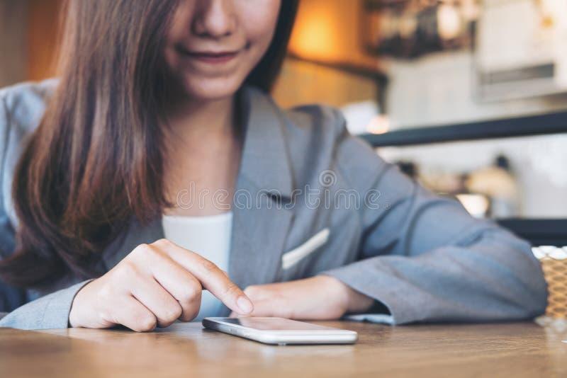 Azjatycka biznesowa kobieta używa mądrze telefon i dotykający zdjęcie stock