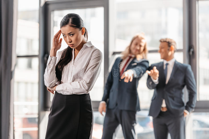 Azjatycka bizneswoman pozycja w biurze, biznesmeni za gestykulować i śmiać się, obraz royalty free