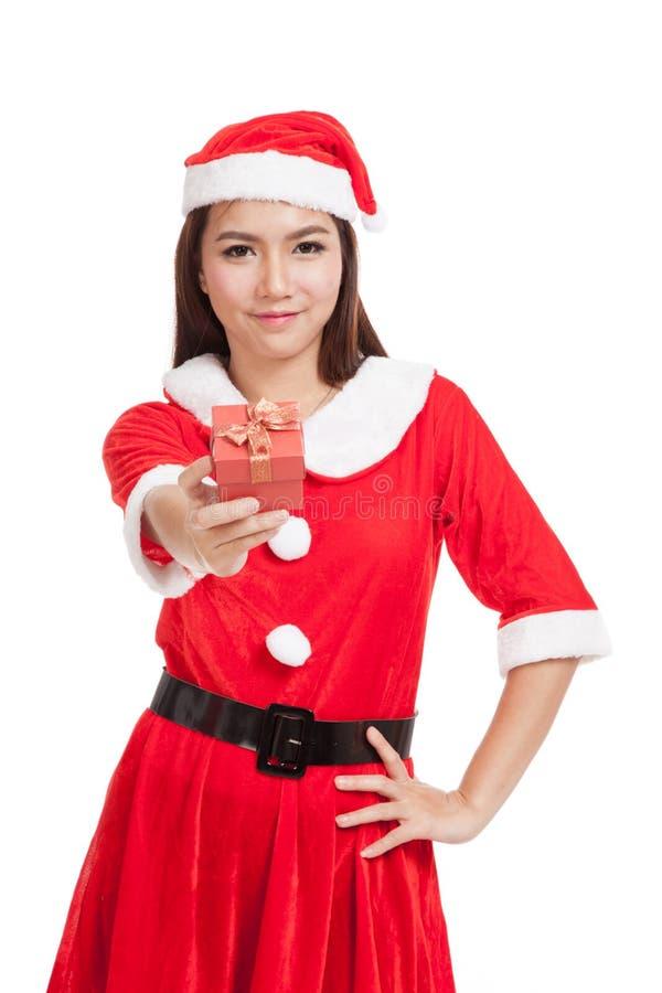 Azjatycka Bożenarodzeniowa dziewczyna z Święty Mikołaj odzieżowym i czerwonym prezenta pudełkiem obraz stock