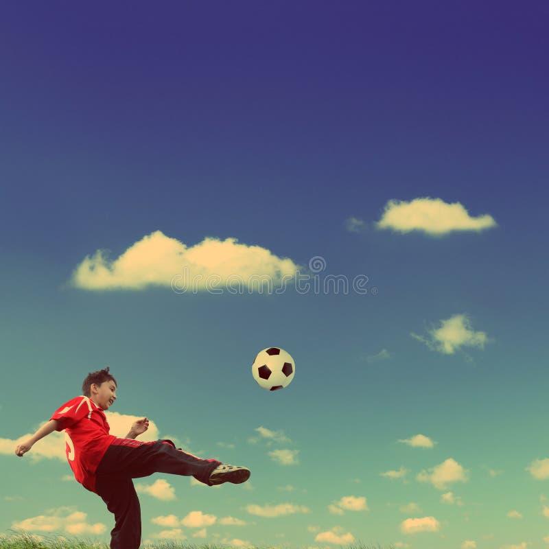 Azjatycka chłopiec bawić się futbol - rocznika retro styl obraz stock