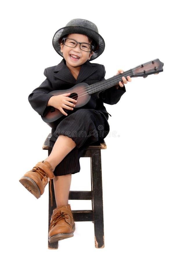 Azjatycka chłopiec bawić się gitarę na odosobnionym białym tle obrazy royalty free