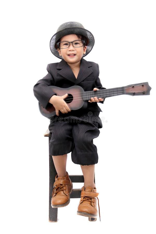 Azjatycka chłopiec bawić się gitarę na odosobnionym białym tle zdjęcia stock