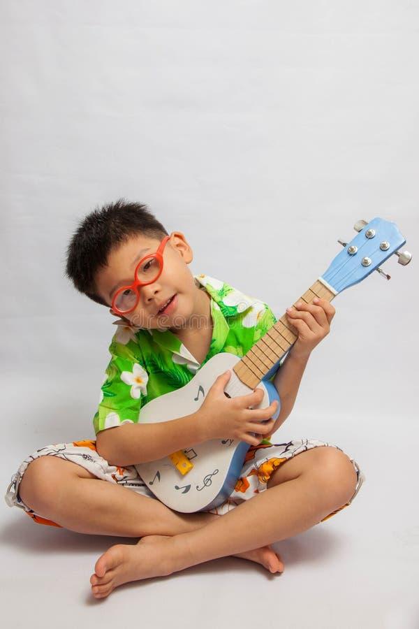 Azjatycka chłopiec bawić się ukulele obraz stock