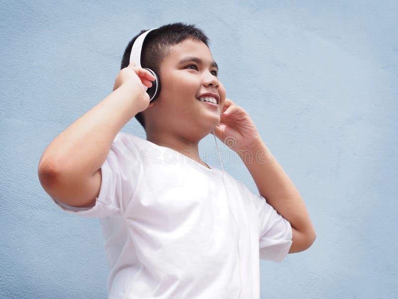Azjatycka chłopiec jest ubranym hełmofon nad błękit ściany tłem obraz stock