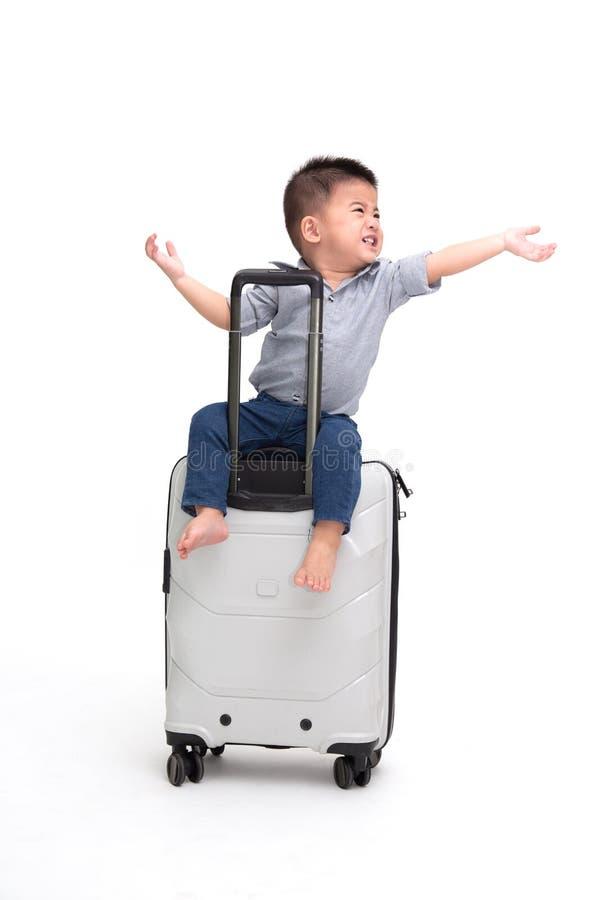 Azjatycka chłopiec obsiadania podróży torba lub walizka odizolowywający na białym tle, zdjęcia stock