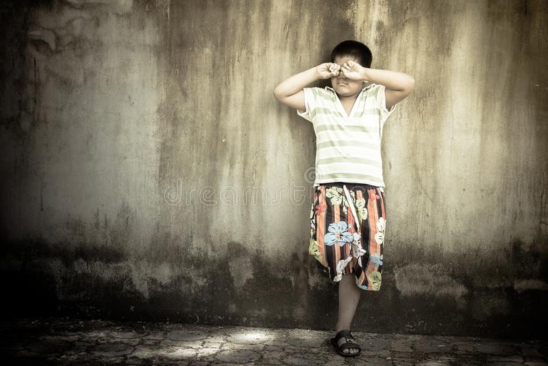 Azjatycka chłopiec płacze samotnie przy starą ścianą, rocznika brzmienie zdjęcia royalty free