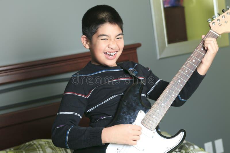 Azjatycka chłopiec sztuki gitara w jego sypialni obrazy royalty free