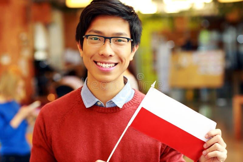 Azjatycka chłopiec trzyma flaga Polska w szkłach obrazy stock