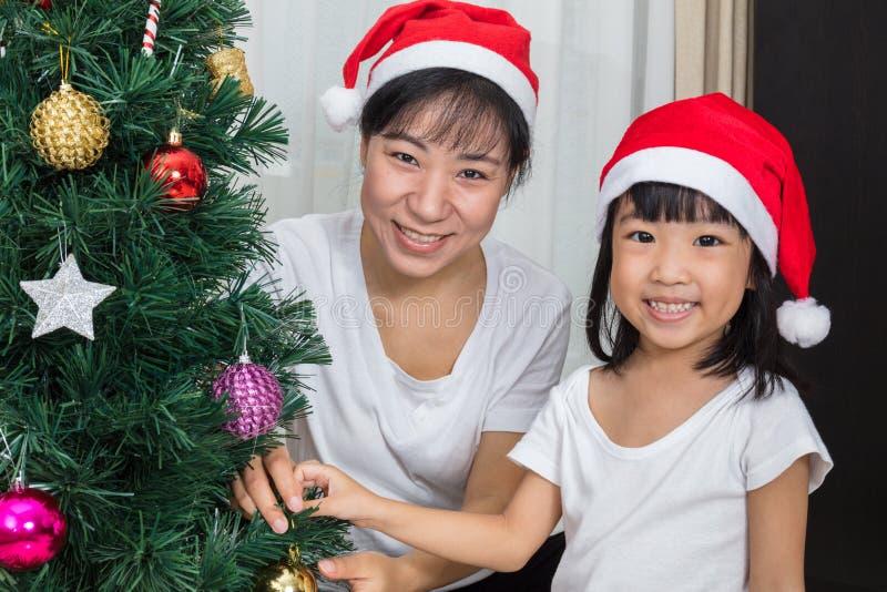 Azjatycka chińczyk matka, córka dekoruje choinki przy h i obrazy stock
