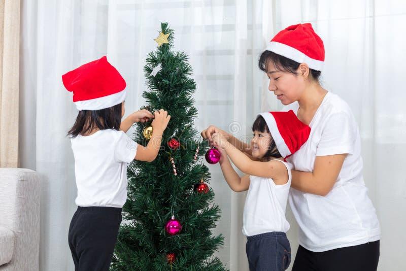 Azjatycka chińczyk matka, córki dekoruje choinki przy i obrazy royalty free