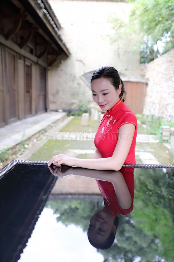 Azjatycka Chińska chi cheongsam kobieta z klasycznym upiększonym fan cieszy się zrelaksowanego czas wolnego w antycznego miastecz obrazy stock