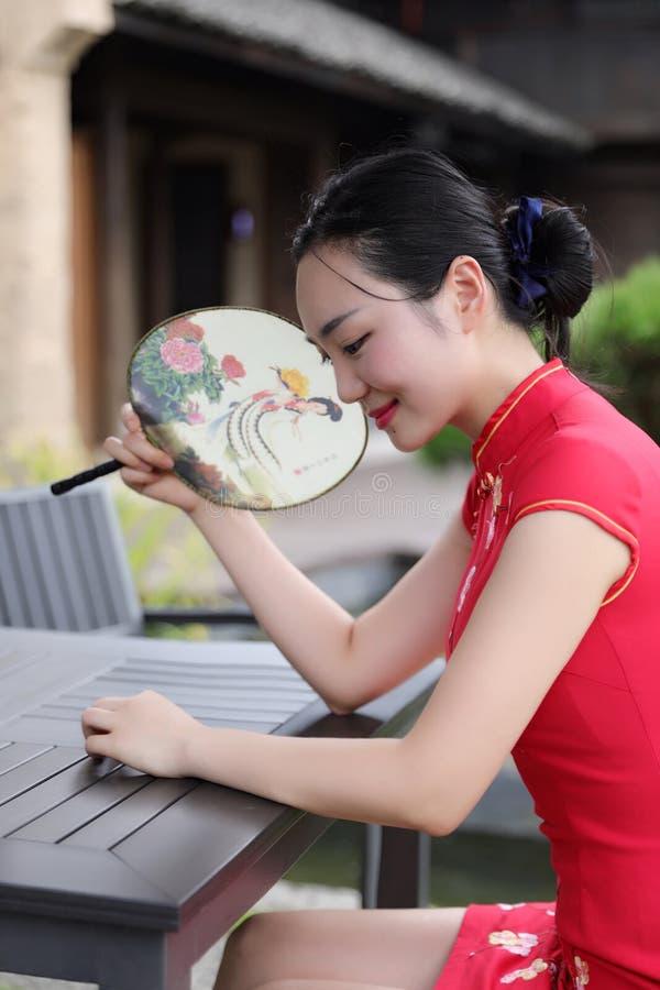 Azjatycka Chińska chi cheongsam kobieta z klasycznym upiększonym fan cieszy się zrelaksowanego czas wolnego w antycznego miastecz fotografia royalty free