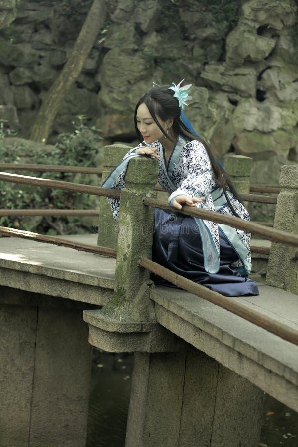 Azjatycka Chińska kobieta w tradycyjnej Błękitnej i białej Hanfu sukni, sztuka w sławnej ogrodowej wspinaczce na przegiętym mosci zdjęcia royalty free