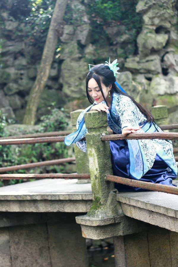 Azjatycka Chińska kobieta w tradycyjnej Błękitnej i białej Hanfu sukni, sztuka w sławnej ogrodowej wspinaczce na przegiętym mosci zdjęcie royalty free