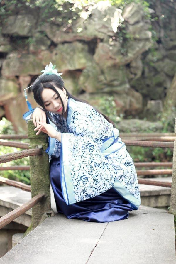 Azjatycka Chińska kobieta w tradycyjnej Błękitnej i białej Hanfu sukni, sztuka w sławnej ogrodowej wspinaczce na przegiętym mosci zdjęcie stock