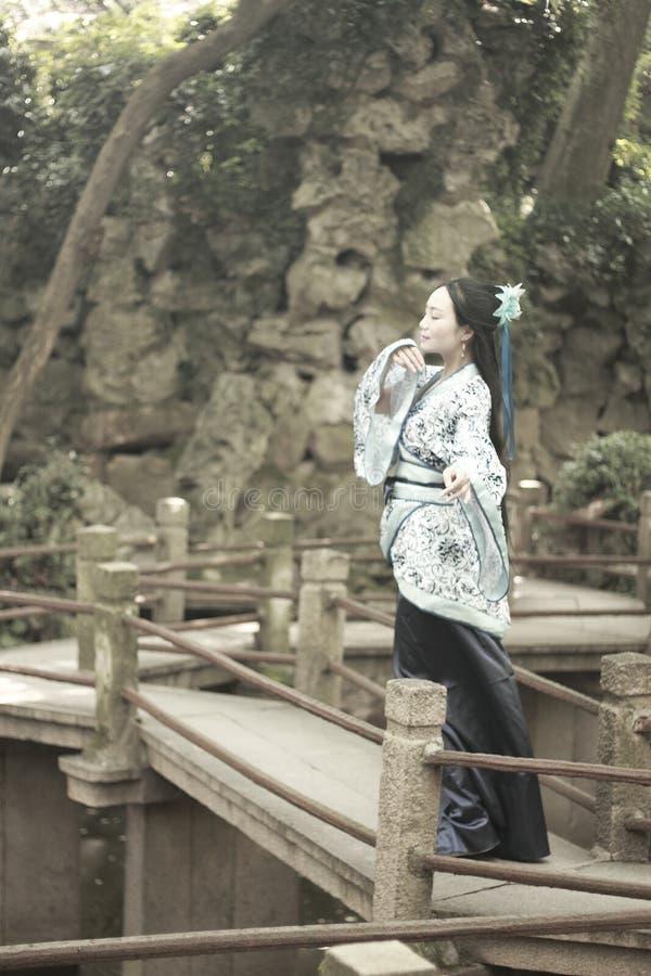Azjatycka Chińska kobieta w tradycyjnej Błękitnej i białej Hanfu sukni, sztuka w sławnym ogródzie na koślawym moscie fotografia royalty free
