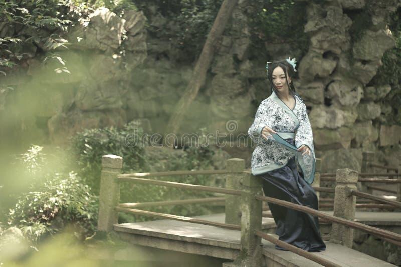 Azjatycka Chińska kobieta w tradycyjnej Błękitnej i białej Hanfu sukni, sztuka w sławnym ogródzie na koślawym moscie obraz stock
