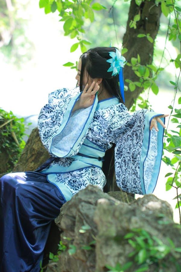 Azjatycka Chińska kobieta w tradycyjnej Błękitnej i białej Hanfu sukni, sztuka w sławnym ogródzie, siedzi na antycznym kamiennym  zdjęcie stock