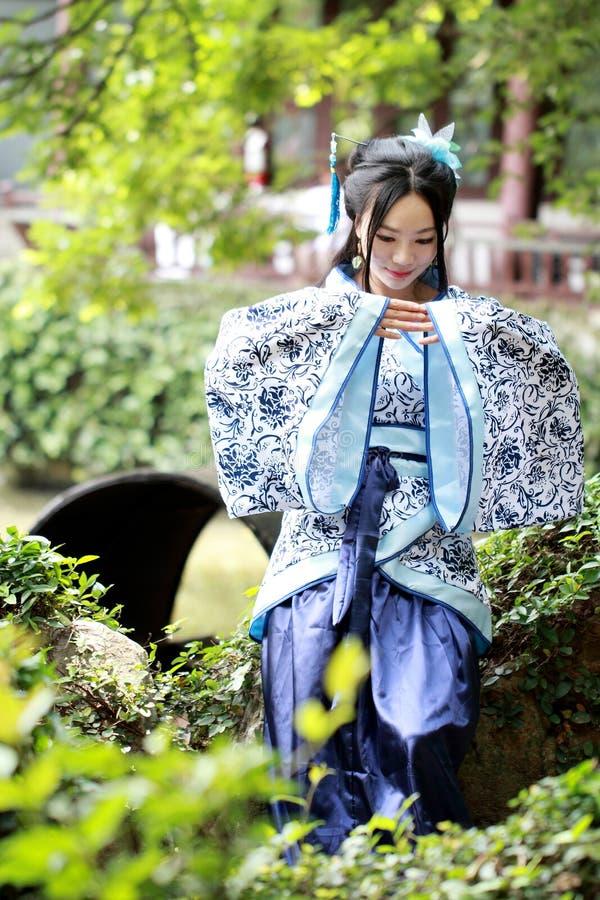 Azjatycka Chińska kobieta w tradycyjnej Błękitnej i białej Hanfu sukni, sztuka w sławnym ogródzie, siedzi na antycznym kamiennym  obraz royalty free
