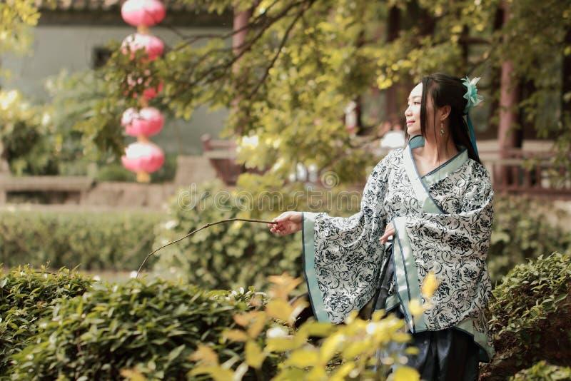 Azjatycka Chińska kobieta w tradycyjnej Błękitnej i białej Hanfu sukni, sztuka w sławnym ogródzie, siedzi na antycznym kamiennym  obrazy royalty free