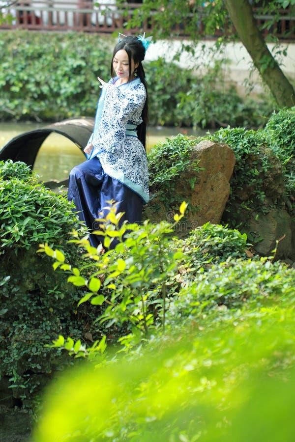 Azjatycka Chińska kobieta w tradycyjnej Błękitnej i białej Hanfu sukni, sztuka w sławnym ogródzie, siedzi na antycznym kamiennym  zdjęcia stock