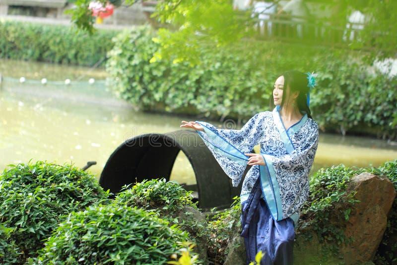 Azjatycka Chińska kobieta w tradycyjnej Błękitnej i białej Hanfu sukni, sztuka w sławnym ogródzie, siedzi na antycznym kamiennym  zdjęcie royalty free