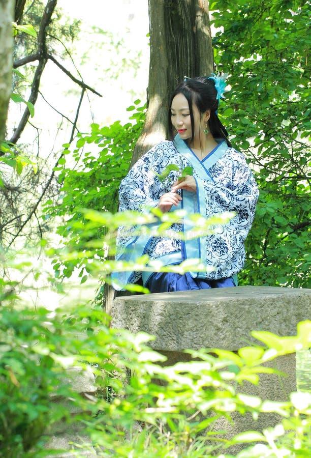 Azjatycka Chińska kobieta w tradycyjnej Błękitnej i białej Hanfu sukni, sztuka w sławnym ogródzie, siedzi na antycznym kamiennym  obraz stock