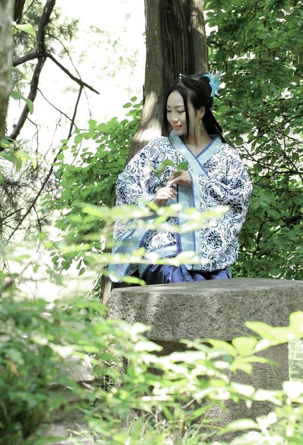 Azjatycka Chińska kobieta w tradycyjnej Błękitnej i białej Hanfu sukni, sztuka w sławnym ogródzie, siedzi na antycznym kamiennym  obrazy stock