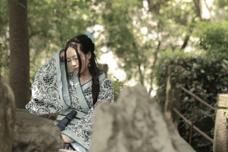 Azjatycka Chińska kobieta w tradycyjnej Błękitnej i białej Hanfu sukni, sztuka w sławnym ogródzie, siedzi na antycznym kamiennym  zdjęcia royalty free
